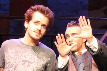 A photo of two actors looking at something; one making a gesture with their hands.