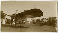 Moisant 29 - Early model single-winged airplane with small propeller sits on grass field, surrounded by crowd of people