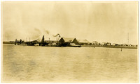 View from across water of dockside cannery facilities and housing facilities in background at Port Moller, Bristol Bay, Alaska