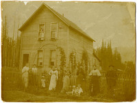 Six women, one man, and four children pose along picket fence in front o fttwo-story farmhouse