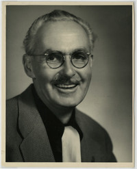 Studio portrait of smiling middle-aged man in spectacles