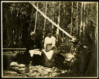 Two women and an elderly man sit on logs with a picnic spread before them