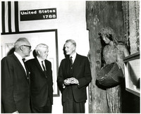 Senator Barry Goldwater and two other men stand together among museum displays