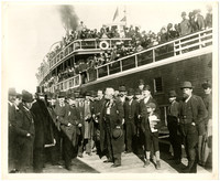 Huge crowd of people, mostly men in suits, overcoats, and derby hats, stand on the Sehome wharf next to large steamer ferry packed with people, all whom gather to send off George Francis Train