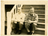 Two men sit next to each other on steps of house