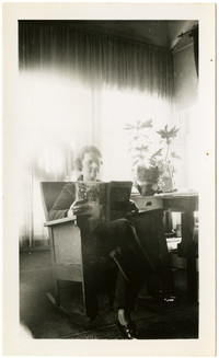 Woman seated in rocking chair, reading a book