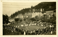 Crowds on bleachers surrounding an athletic field watch a dance performance on grounds of Bellingham Normal School with Old Main in background