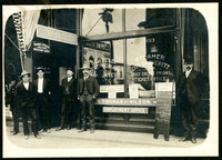 Six men stand in front of storefront with several businesses advertised on signs and windows, including Steamer - City of Everett - Ticket Office, and real estate and insurance offices