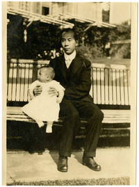 Unidentified Asian man and child sit on park bench