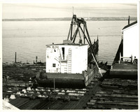 White two story structure on barge in dry dock looking across Bellingham Bay toward the cement plant.
