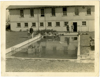 Cement pond in back yard shows small-scale representation of Pacific American Fisheries facilities with several people looking on