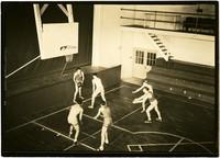 Six men play basketball in Whatcom High School gymnasium