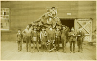 Nine men stand in front of a pile of split logs, two men sit on top, with a warehouse behind them