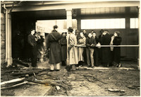 A crowd stands in and around rubble of burned remains of Fairhaven High School