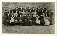 Teenage school children pose seated and standing in four rows with their teacher in front of brick building