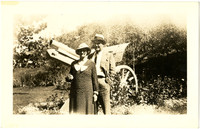 Man and woman pose in park-like setting with canon on display behind them