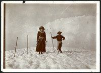 Two unidentified people, a woman and young boy, standing on top of snow-covered mountain