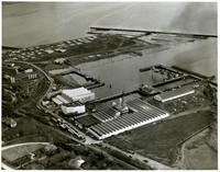 Aerial view of industrial waterfront, Bellingham, WA, showing landfill area used as lumber storage, several warehouses, and boat moorage