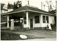 "Small, two-pump service station with ""Grand Vista Service"" sign on roof"