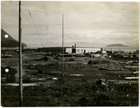 Industrial debris dots coastal field with warehouse in background and snowy mountain peaks across the water on the horizon