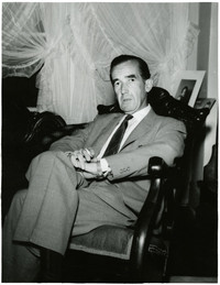 Edward R. Murrow sits in rocking chair in parlor of his mother's house, Bellingham, Washington