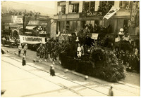 """Parade travels down Holly Street, downtown Bellingham, WA, with young women standing on float accompanied by young women carrying """"Fairhaven"""" banner"""