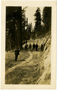 Chuckanut Drive construction -  - seven men in suits stand on roadway on forested hillside