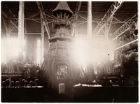 """Warehouse-style exhibition hall with large commemorative structure in conical form from thatch and wood, surrounded by tables displaying goods and products, with large sign of """"State of Washington"""" partially visible at right"""