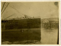 """Three men stand on bow of ship """"City of Puebla"""" near a dock where a small crowd awaits"""