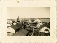 View over rooftops of Pacific American Fisheries Naknek Cannery, Alaska, with boardwalks between buildings, water in distance