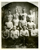 Twelve men in athletic shirts pose in three rows in studio portrait