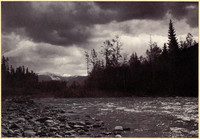 The Nooksack River flows past rocky bank with forest in background and Mt. Baker on horizon