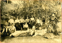 Revelers pose around large picnic blanket wearing silly hats and palm-frond skirts