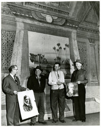 Four men stand together in front of Egyptian-themed mural, with two of the men displaying studio portraits