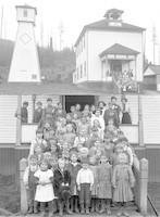 Two photos of two-story schoolhouse with approximately sixty students and two teachers.
