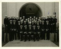 A group of about forty Navy men in uniforms, both officers and sailors, pose in several rows, with an arrow drawn to indicate Gunnar Anderson