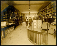 Sixteen men pose in line across store selling paint and wallpaper