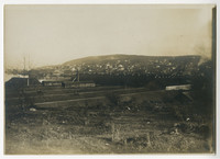 Unidentified location with scrubland in foreground, bunker-like mounds in rows beyond, town on hillside in distance