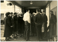 A group of Fairhaven High School students, most facing away from the camera,  wearing coats and hats, standing together in an outside, covered area, probably part of a school