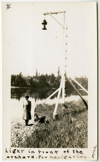 Woman in long coat and hat stands at shoreline next to grassy field next to tall wooden lamp post