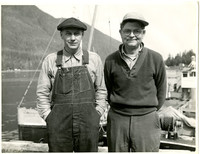 Two men pose together on dock with boats, water, and forested mountain ni background
