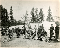 Soldiers and military band members relax outside row of tents in forest camp