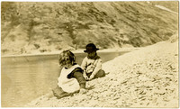 Helen Smith and Adriau - two children sit on shore of rocky beach