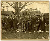Fifteen men and one boy pose holding goeducks or other large mollusk with shells scattered at their feet