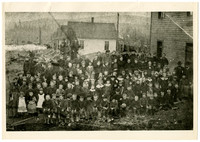 First Sehome School - Large group of young students and several students pose outside with several row houses in background and forested hills beyond