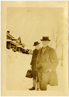 Two men in suits and long coats on sidewalk  along residential street in deep snow