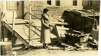 Unidentified woman in fur-collared coat stands in front of industrial building