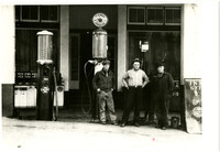 Three men stand in front of gasoline pumps outside service station