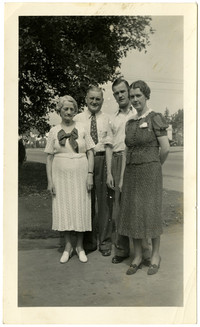 Young couple and older couple pose on sidewalk