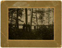 Three men stand among trees with lake in background